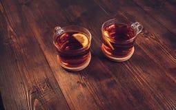 Twee volledige koppen van zwarte thee met citroen stock fotografie