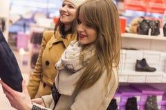 Twee volwassen meisjes in een schoenopslag royalty-vrije stock afbeelding
