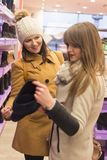 Twee volwassen meisjes in een schoenopslag stock fotografie
