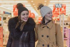 Twee volwassen meisjes verlaten de opslag royalty-vrije stock afbeelding