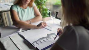 Twee volwassen vrouwen hebben een commerciële vergadering en het werk met documenten in restaurant stock footage