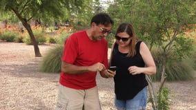 Twee Volwassenen spelen Vergroot Werkelijkheidsspel op Smartphone stock footage