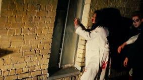Twee vreselijke zombieën die donkere straat lopen bij nacht het verbergen achter verlaten huis stock video