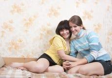 Twee vreugdemeisje op bank stock foto