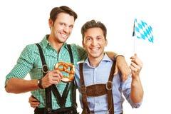 Twee vrienden in Beieren met pretzel Stock Afbeeldingen