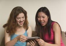 Twee vrienden die bij foto's lachen stock foto