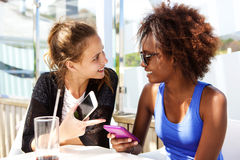 Twee vrienden die bij restaurant met mobiele telefoon zitten Stock Foto