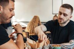 Twee vrienden die burgers en frieten, het drinken koffie bij koffie eten stock foto's