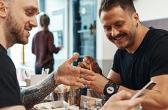 Twee vrienden die burgers eten frieten, hebbend pret en glimlachend bij koffie royalty-vrije stock fotografie