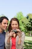 Twee vrienden die de fotoinzameling bekijken in haar camera Stock Foto