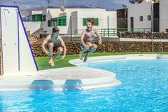 Twee vrienden die in de pool springen Royalty-vrije Stock Foto's