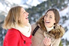 Twee vrienden die in de wintervakantie lachen stock fotografie