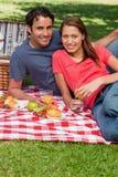 Twee vrienden die glazen houden terwijl het vooruitzien tijdens een picknick Stock Foto