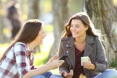 Twee vrienden die houdend hun slimme telefoons spreken stock foto's