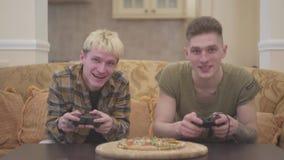 Twee vrienden die op de bank in de woonkamer en het spelen videospelletje met enthousiasme het glimlachen holdings binnen bedieni stock video