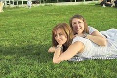 Twee vrienden die op het gazon liggen stock afbeeldingen