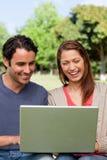 Twee vrienden die op iets op een tablet letten Stock Foto
