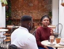 Twee vrienden die over dranken in een in koffiebinnenplaats spreken stock afbeeldingen