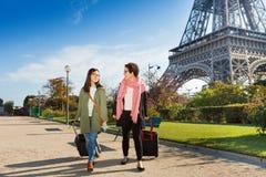 Twee vrienden die rond Parijs met bagage lopen stock foto