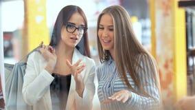 Twee vrienden die van de schoonheids jonge vrouw iets achter storefront in een winkelcomplex bespreken stock video