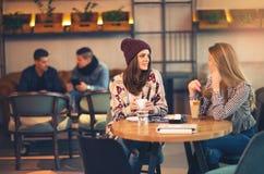 Twee vrienden die van koffie samen in een koffiewinkel genieten royalty-vrije stock afbeeldingen