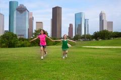 Twee vrienden die van zustermeisjes holding leiden dienen stedelijke horizon in stock foto