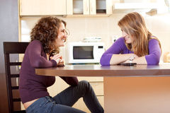 Twee vrienden die zitting op een keukenlijst babbelen stock afbeeldingen