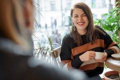 Twee vrienden in een koffie door het venster royalty-vrije stock afbeelding