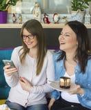 Twee vrienden lachen en genieten van cakes stock foto's