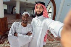 Twee vrienden van de de jonge mensenliefde van Arabis selfie met smartphone stock foto