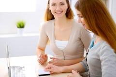 Twee vrienden of zusters die nemend een gesprek bij de lijst met laptop spreken Royalty-vrije Stock Afbeelding