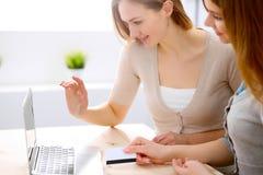 Twee vrienden of zusters die nemend een gesprek bij de lijst met laptop spreken Stock Afbeeldingen