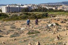 Twee vriendengangen in volgende historisch graf in grote uitgraving in Paphos, wordt genoemd Graven van de Koningen en het is zee stock foto's