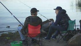 Twee vriendenvisser die en het drinken bier, rustend weekend, goed bedrijf vissen stock video