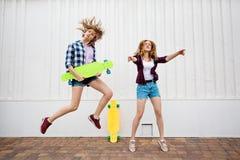 Twee vrij blonde meisjes die geruite overhemden en denimborrels dragen springen en dansen met heldere longboards jong stock foto's