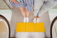 Twee vrij jonge slanke meisjes met donker haar, die toevallige stijl dragen, bevinden zich bij de roltrap naast elkaar in modern stock foto