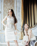 Twee vrij tweelingzusters blonde krullende kapsels in luxe huisvesten binnenland samen, rijk jongerenconcept royalty-vrije stock afbeeldingen