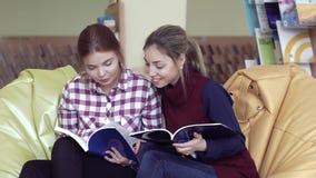 Twee vrij universitaire meisjes die in bibliotheek zitten en boeken onderzoeken stock video