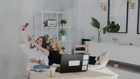 Twee vrij vrouwelijke jaren '30vrienden hebben pret en ontspannen in de werkplaats De donkerbruine vrouw maakt selfie op smartpho stock videobeelden