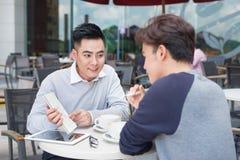 Twee vrolijke Aziatische bedrijfsmensen die met documenten bespreken Royalty-vrije Stock Foto