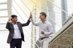 Twee vrolijke bedrijfs elkaar slaan overhandigt en mensen die glimlachen Stock Afbeeldingen