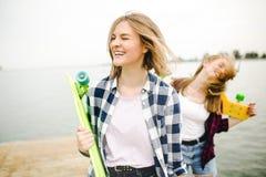 Twee vrolijke gelukkige schaatsermeisjes in hipsteruitrusting die pret op een houten pijler hebben tijdens de zomervakantie stock foto