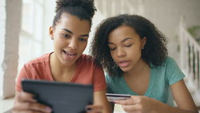 Twee vrolijke gemengde ras krullende meisjes die online met tabletcomputer en creditcard thuis winkelen stock footage