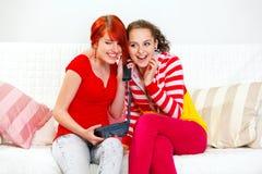 Twee vrolijke jonge meisjes die op telefoon spreken stock afbeelding