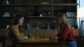 Twee vrolijke jonge vrouwen die schaak thuis spelen stock videobeelden