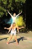 Twee vrolijke jonge vrouwenvrienden die pret met het exploderen Holi hebben pow Stock Foto's