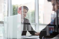 Twee vrolijke jonge zakenlieden met laptop op commerciële vergadering Royalty-vrije Stock Foto's
