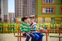 Twee vrolijke jongens in t-shirts spelen op een grote ijzercarrousel op de speelplaats bij de de zomer of de lente warme dag in k royalty-vrije stock afbeelding