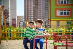 Twee vrolijke jongens in t-shirts spelen op een grote ijzercarrousel op de speelplaats bij de de zomer of de lente warme dag in k royalty-vrije stock foto's