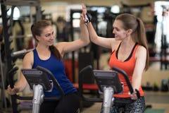 Twee vrolijke meisjes die samen in de club van de gymnastieksport uitoefenen royalty-vrije stock afbeelding